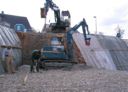 Nach dem Baugrubenaushub wird der Minibagger aus der abgetreppten Baugrube gehoben
