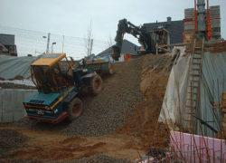Der Radlader wird zum einbringen der Sauberkeitsschicht in die Baugrube hinabgelassen