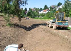Fertiggestelltes Bachbett und wieder hergestellter Fußweg mit Auslaufspiegel aus Wasserbausteinen